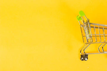 grocery cart on a yellow background, concept of buying business finance