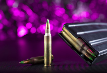 M855 ammo and metal magazine with purple behind
