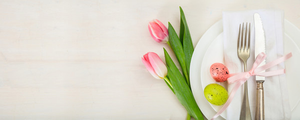 Easter table setting with pink tulips on white wooden background. Top view, copy space, banner