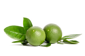 two green limes with leaves isolated on white background