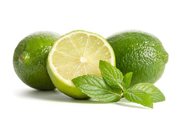 two limes with half of a juicy lime with leaves of mint isolated on white background