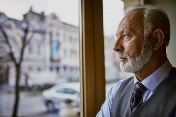 Portrait of senior man looking through window Wall mural