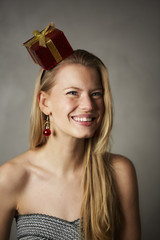Christmas lady with gift on head, smiling