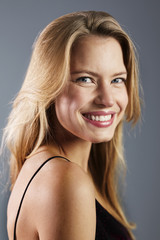 Beautiful and blond young woman smiling, studio