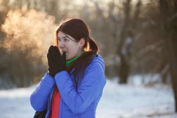 Picture of brunette warming hands in winter at woods