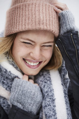Beautiful woman in winter clothing laughing, eyes closed
