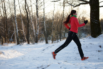 Image of sports woman on run through winter forest
