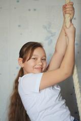 Cute teenager girl 12-years old posing near gymnastic rope