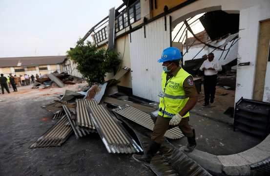 A police officer carries his equipments in a box after inspecting an old tea warehouse collapsed in Colombo