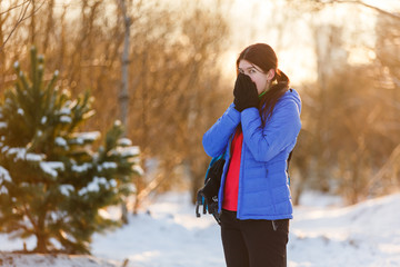 Picture of sports woman with backpack of warming hand