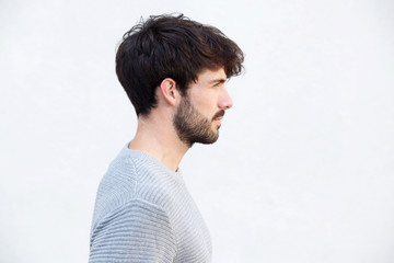 Close up profile handsome young man by white wall