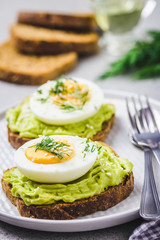 Soft boiled egg and avocado toasts on concrete background. Selective focus, close up, space for text.