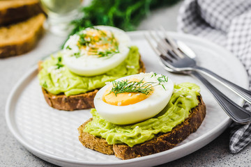 Avocado toast with eggs on concrete background. Selective focus, close up, space for text.