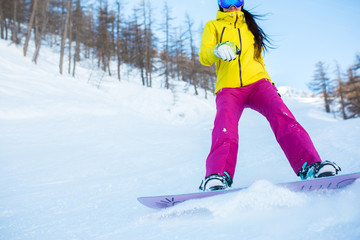 Picture of athlete girl in helmet and mask snowboarding from snowy slope with trees