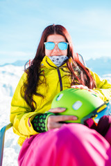 Portrait of sports long-haired woman with helmet resting on armchair in winter resort