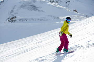 Photo of female athlete wearing helmet and mask, snowboarding from mountain slope