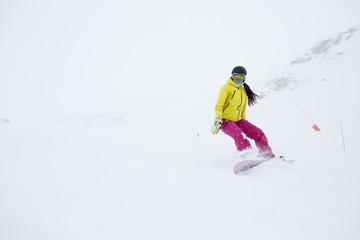 Image of athlete girl in helmet with developing hair, snowboarding from mountain slope