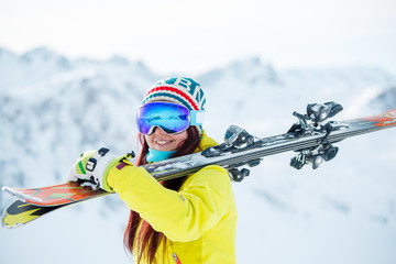 Portrait of smiling woman in mask with skis on her shoulder