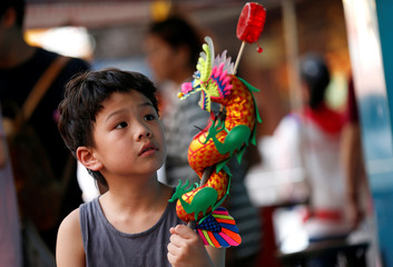 A boy plays with a Chinese dragon toy in Chinatwon in Bangkok