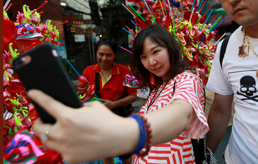 A Chinese tourist takes a selfie photo as she buys Chinese traditional dragon toys in Chinatwon in Bangkok
