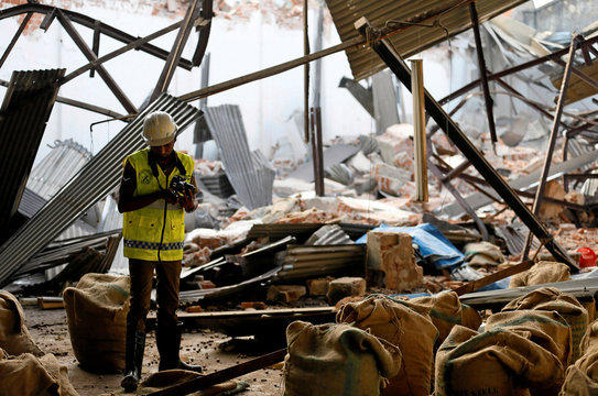 A police officer inspects the collapsed old tea warehouse in Colombo
