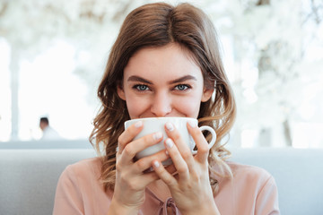 Portrait of a smiling young woman holding cup of coffee