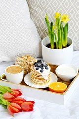 Cup with Cappuccino and Homemade Pancakes Sour Cream Berries Granola Orange Healthy Breakfast Morning Concept Woman's  Day Flowers Tulips Daffodils