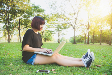 Young asian woman's legs on the green grass with open laptop. Girl's hands on keyboard. Distance learning concept. Happy hipster young asian woman working on laptop in park. Student studying outdoors.
