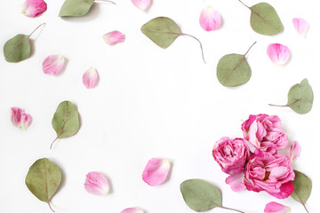 Styled stock photo. Feminine wedding desktop composition with pink roses petals and flowers, dry green eucalyptus leaves and white background. Floral pattern. Empty space. Top view. Picture for blog.