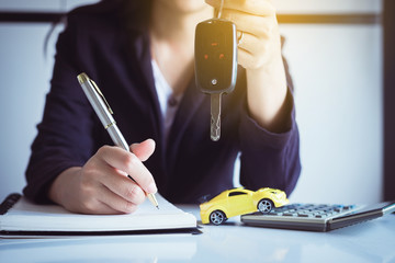 Car key on hand with auto dealership and rental ,Car finance concept