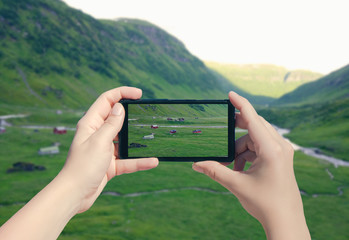 Picture Norway on mobile phone. Female take photo of Suleskard on smart phone