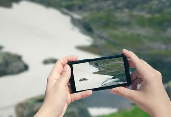 Picture of snow in Norway on mobile phone. Female take photo of Suleskard on smart phone