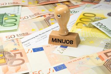 Eine Lohnabrechnung, Euro Geldscheine und ein Stempel mit dem Aufdruck Minijob