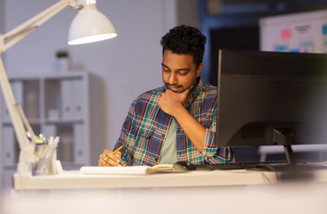 creative man with notebook working at night office