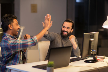 creative team making high five at night office