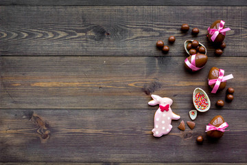 Easter composition. Easter sweet gift. Chocolate eggs near cookies in shape of Easter bunny on dark wooden background top view space for text