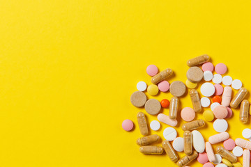 Medication white colorful round tablets arranged abstract on yellow color background. Aspirin, capsule pills for design. Health, treatment, choice healthy lifestyle concept. Copy space advertisement.
