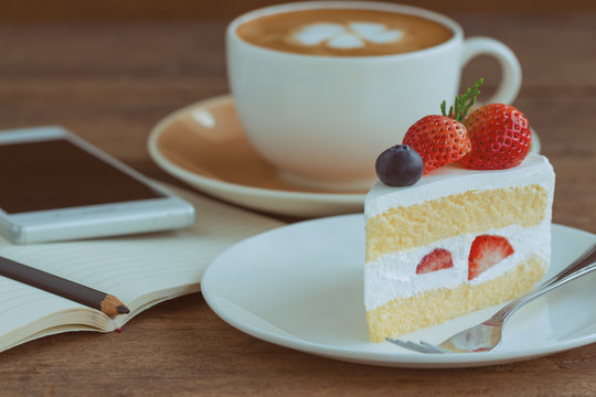 Homemade delicious and soft strawberry shortcake on wood table beside smartphone and hot cappuccino coffee at bakery shop or cafe restaurant. Vanilla sponge cake with whipped cream and strawberries.