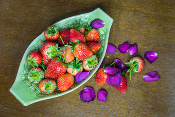 Strawberries and Rose petals in a boat bowl on rustic wood.