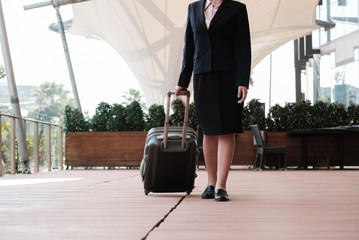 businesswoman pulling luggage outdoors. woman carrying baggage for business trip. asian female holding trolley case.