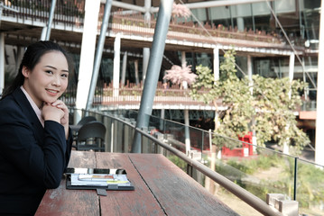 confident businesswoman relaxing outside office building. young female entrepreneur woman working on balcony. people, business concept