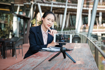 businesswoman use smartphone for online live streaming. woman recording video blog. vlogger presenting business vlog.