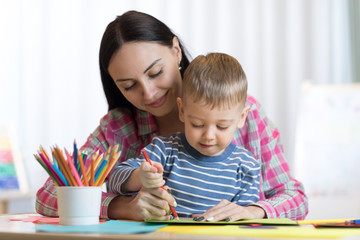 Blond smiling child little boy hold in hand pencil drawing something together with mom.