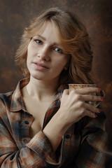 Young beautiful woman in plaid shirt with coffee mug .