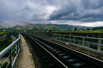 Picturesque fairy tale landscape with a view at railway bridge and mountains covered with stormy rainy clouds. Fantasy colorful scenic route Hills and river. Tourist destination in Carpathians.