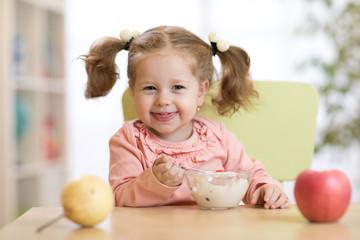 child girl eating healthy food at home or kindergarten