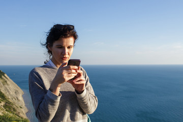 beautiful brunette woman on hill over sea using smartphone