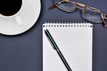Office desk with open notepad, pen, eyeglasses and coffee cup