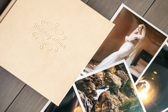 White leather wedding album and printed photos with the bride and groom
