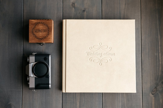 White leather wedding album, wooden box with inscription Wedding day and vintage photo camera
